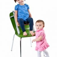 SCI SVAN Lyft Booster Seat Natural on Green Chair with Girl and Baby