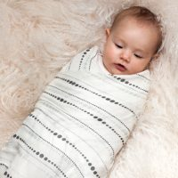 A baby swaddled in the Moonlight Bamboo Swaddling Blanket by Aden and Anais