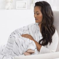 A mother using the Aden and Anais Moonlight Swaddling Blankets are a Nursing Cover
