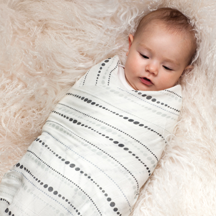 0f8561e43e A baby swaddled in the Moonlight Bamboo Swaddling Blanket by Aden and Anais